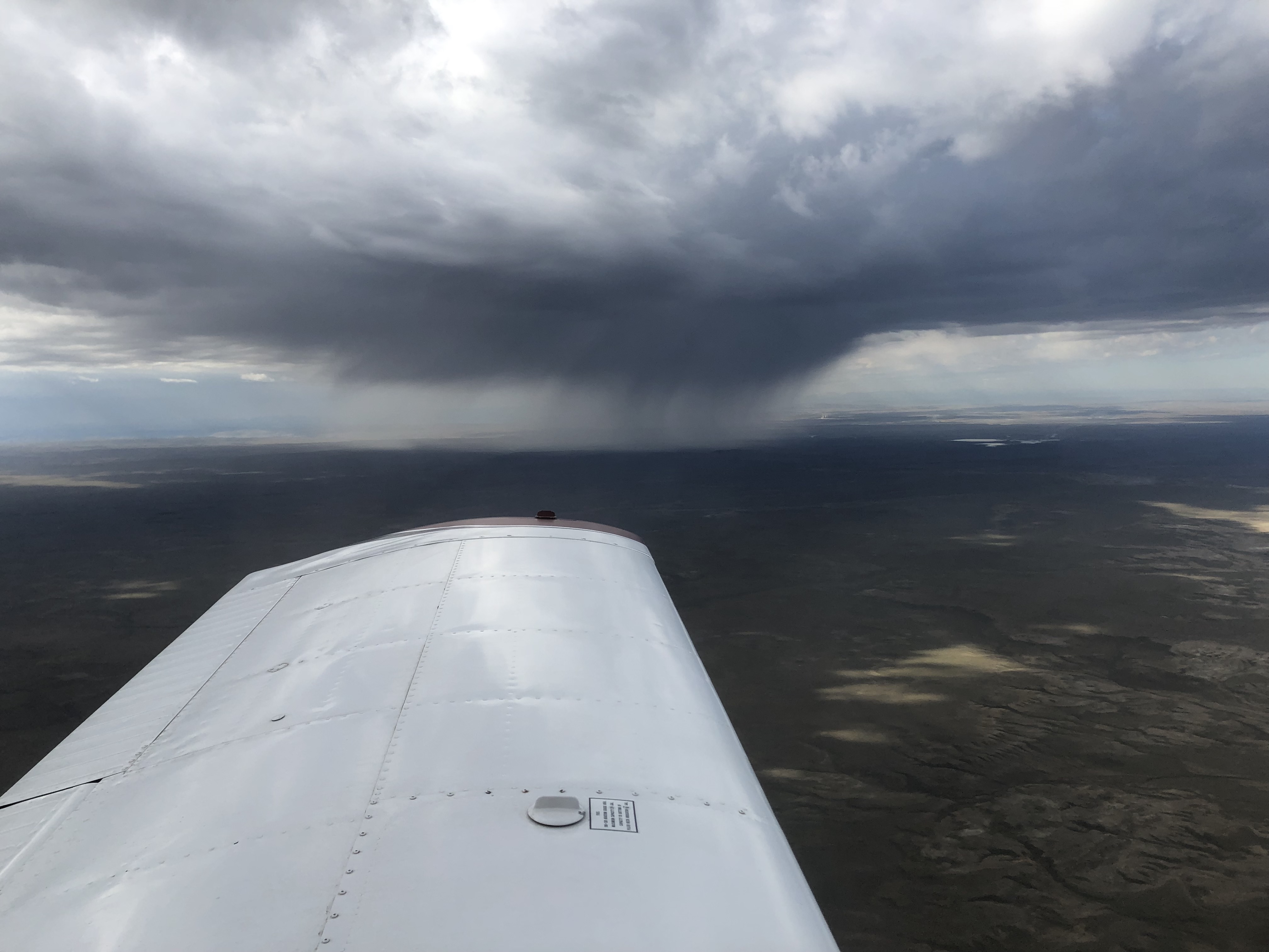 A thunderstorm dropping rain far to the left of this airplane